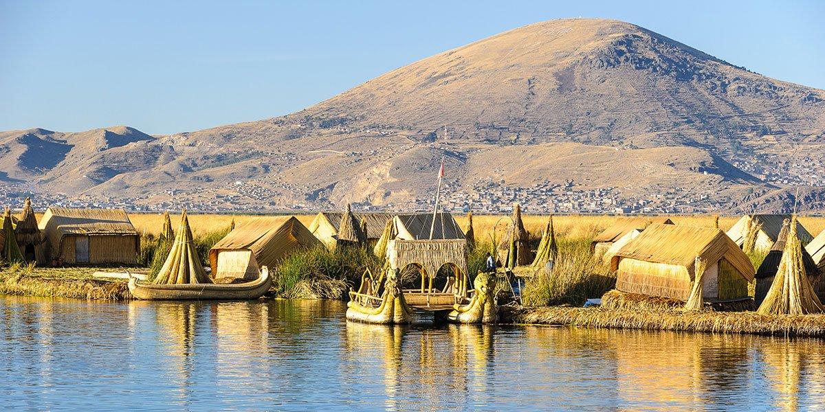 Bild från en av Urusörna i Peru. Öarna är konstgjorda och byggda i vass. Vassbåtar i förgrunden.